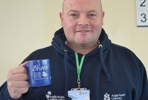 Chronic back pain dean walker holding mug  photo provided by patient for website listing